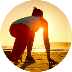 Woman on beach crouched in starting position to run